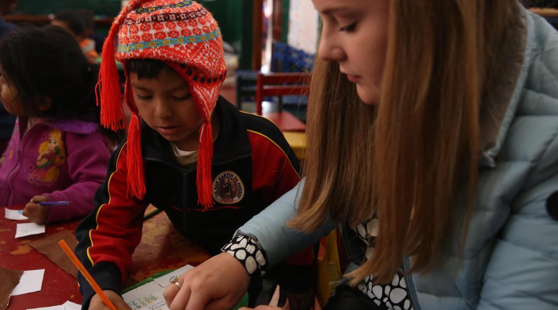 Voluntaria social en Perú ayudando a un niño durante una sesión de manualidades de su voluntariado para jóvenes.